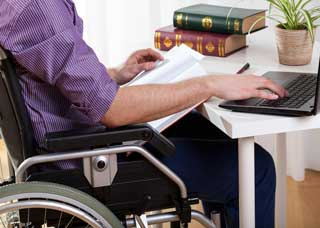 Image of a person in a wheelchair using the computer