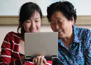 Image of a grandma and granddaughter reading a computer screen