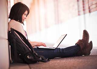 Image of a teen sitting on the ground, using a laptop