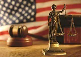 Image of Lady Justice with a gavel and American flag in the background