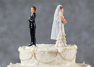 Image of a bride and groom wedding cake toppers with their backs to each other
