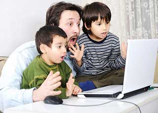 Image of a man with two sons looking at a laptop