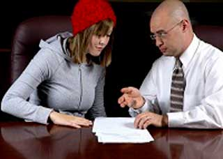 Image of a man helping a young woman fill out a document